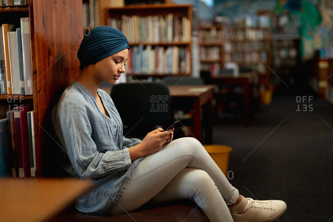 Side view close up of a young Asian female student wearing a turban using a smartphone in a library