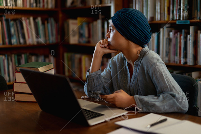 Side view close up of a young Asian female student wearing a turban using a laptop computer and studying in a library