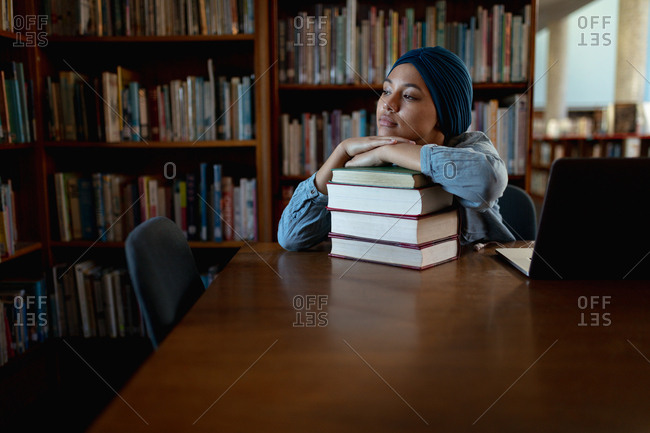 Front view close up of a young Asian female student wearing a turban resting on a pile of books and studying in a library