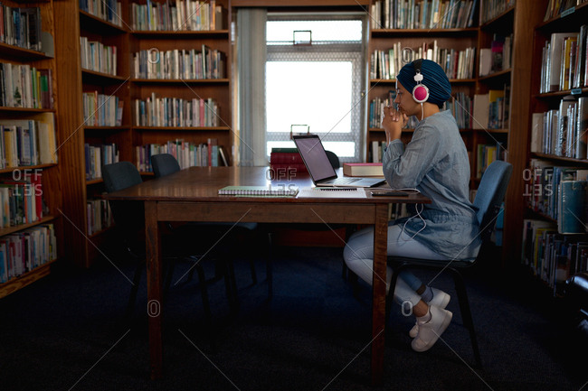 Side view of a young Asian female student wearing a turban and headphones, using a laptop computer and studying in a library