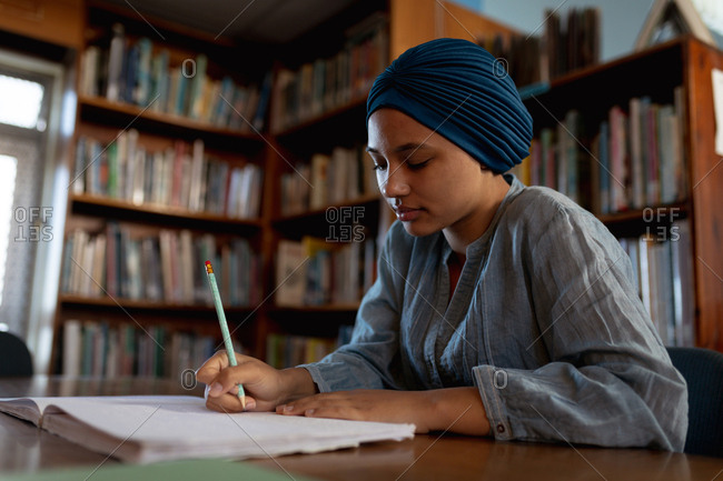 Side view close up of a young Asian female student wearing a turban writing and studying in a library