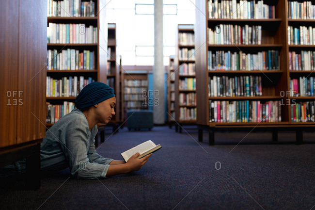 Side view of a young Asian female student wearing a turban reading a book, lying on a floor and studying in a library