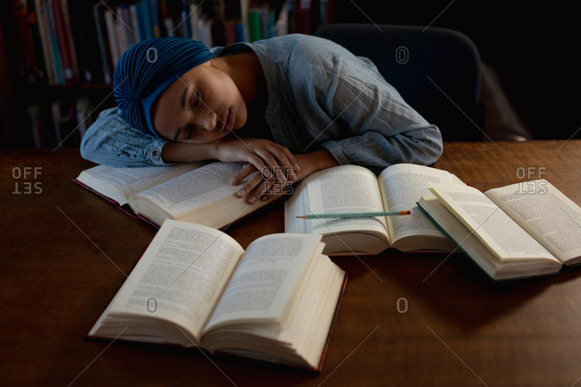 Front view close up of a young Asian female student wearing a turban asleep on a table surrounded by books during studying in a library