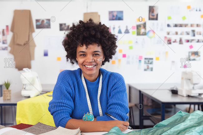 Portrait of a young mixed race female fashion student working on a design in a studio at fashion college