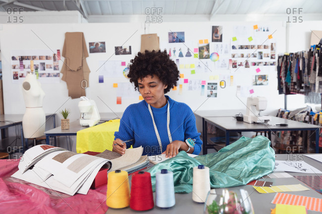 Front view of a young mixed race female fashion student working on a design in a studio at fashion college