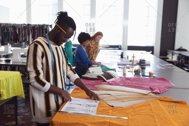 Side view of a young African American male fashion student working on a design in a studio at fashion college, with female students working in the background