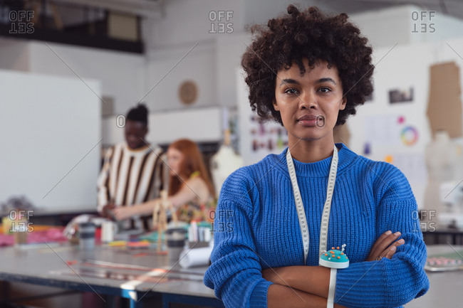 Portrait close up of a young mixed race female fashion student looking straight to camera in a studio at fashion college, with students working in the background