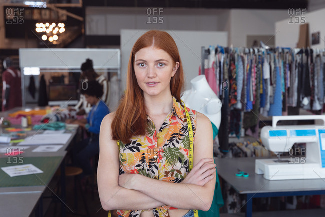 Front view of a young Caucasian female fashion student standing with arms crossed in a studio at fashion college