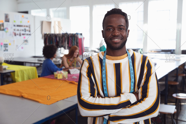 Portrait of a young African American male fashion student standing with arms crossed in a studio at fashion college