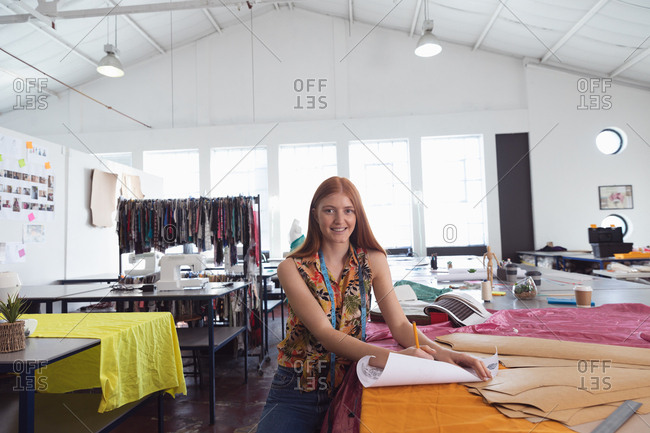 Portrait of a young Caucasian female fashion student smiling to camera while working on a design in a studio at fashion college