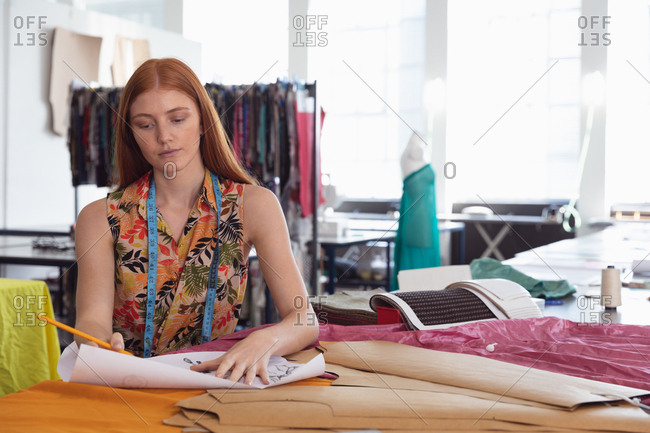 Front view of a young Caucasian female fashion student working on a design in a studio at fashion college