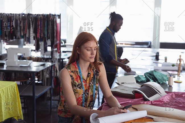 Front view of a young Caucasian female fashion student working on a design in a studio at fashion college, with a male student working in the background