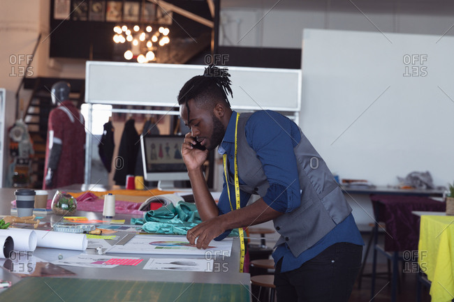 Side view of a young African American male fashion student talking on a smartphone and working on a design in a studio at fashion college