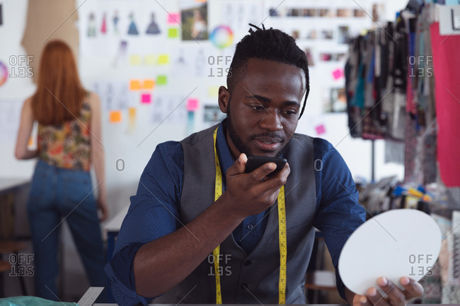 Front view close up of a young African American male fashion student holding and talking on a smartphone working on a design in a studio at fashion college