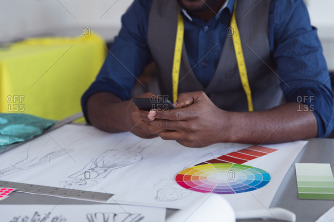Front view mid section of a young African American male fashion student using a smartphone while working on a design in a studio at fashion college