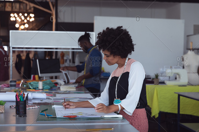 Side view of a young mixed race female fashion student working on a design in a studio at fashion college, with a male student working in the background