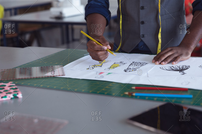 Front view mid section of a young African American male fashion student working on a design in a studio at fashion college