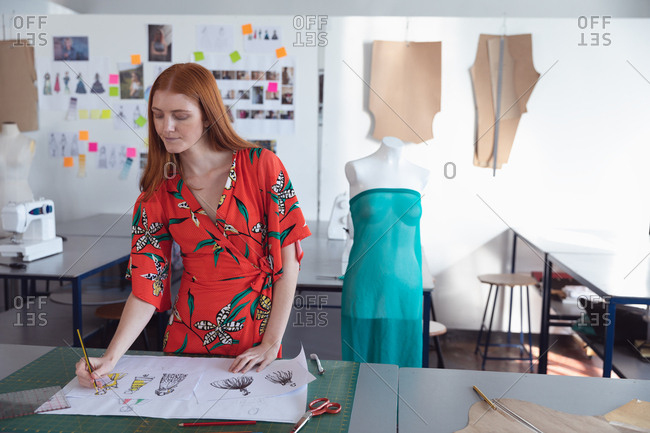 Front view of a young Caucasian female fashion student standing working on a design in a studio at fashion college, with a mannequin in the background