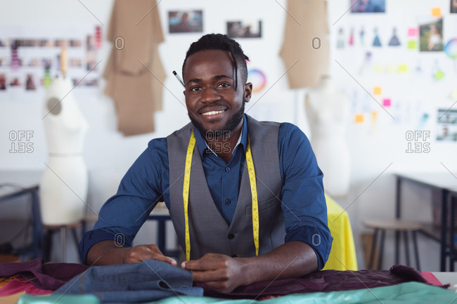 Portrait of a young African American male fashion student with a tape measure around his neck smiling to camera and working on a design in a studio at fashion college