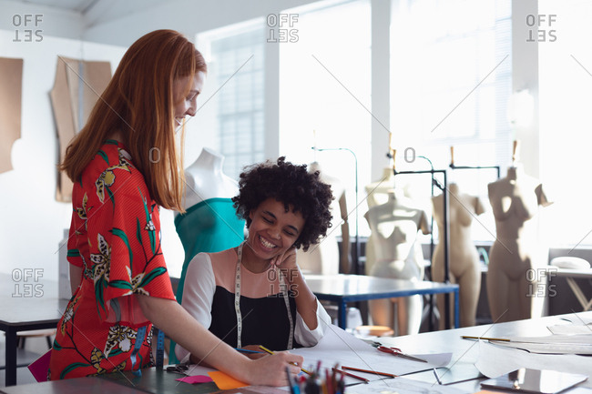 Front view of a young mixed race female fashion student sitting at a desk working on a design and talking to a young Caucasian female colleague standing beside her in a studio at fashion college with mannequins in the background
