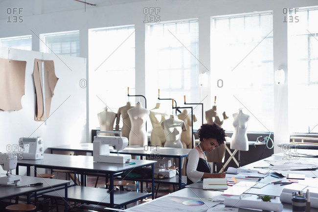Side view of a young mixed race female fashion student sitting at a table working on a design in a studio at fashion college with mannequins in the background