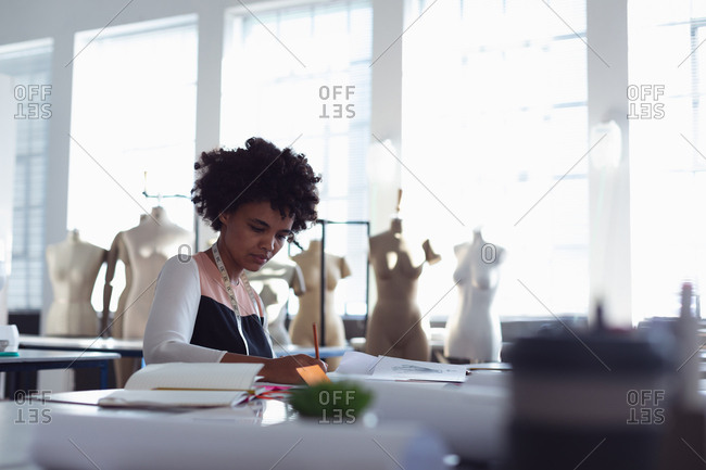 Front view of a young mixed race female fashion student sitting at a table working on a design in a studio at fashion college