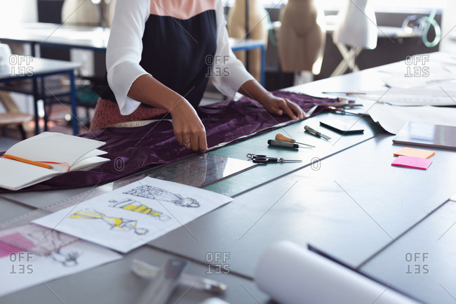Front view mid section of a young mixed race female fashion student measuring fabric on a table while working on a design in a studio at fashion college