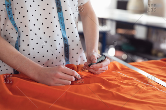 Front view mid section of a young Caucasian female fashion student working on a design with orange fabric in a studio at fashion college