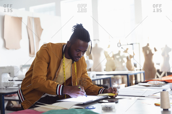 Side view of a young African American male fashion student working on a design using a tablet and a stylus in a studio at fashion college