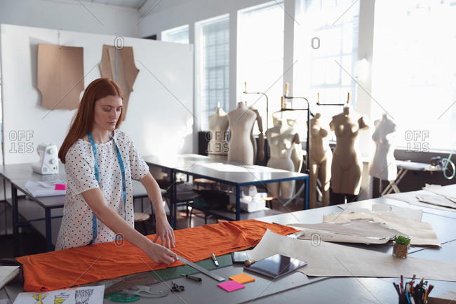 Side view of a young Caucasian female fashion student working on a design measuring orange fabric in a studio at fashion college, with mannequins in the background
