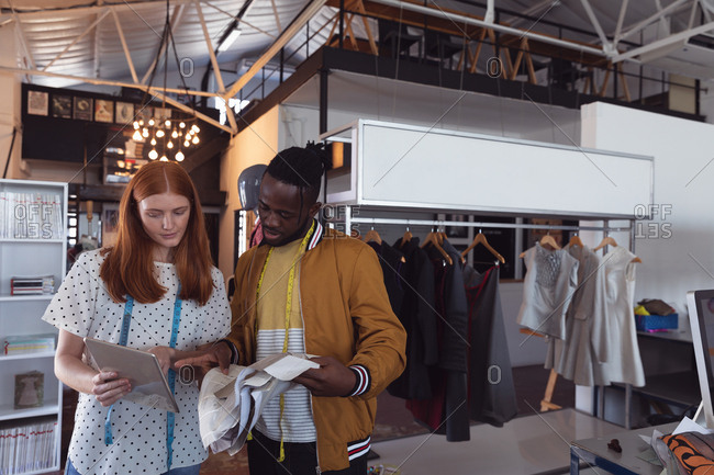 Front view of a young African American male fashion student and a young Caucasian female fashion student looking at a tablet computer together while working on a design in a studio at fashion college