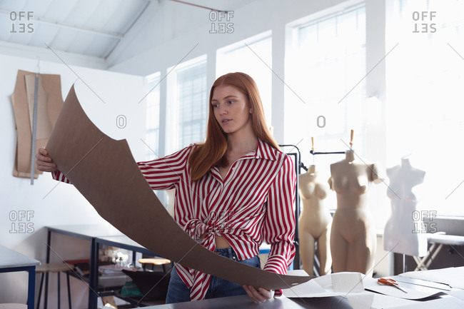 Front view of a young Caucasian female fashion student holding a pattern while working on a design in a studio at fashion college