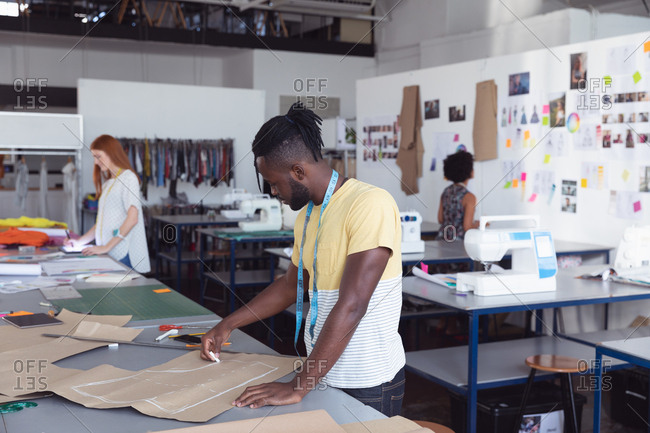 Side view of a young African American Caucasian male fashion student drawing a pattern while working on a design in a studio at fashion college, with other students working in the background