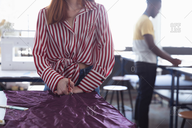 Front view mid section of a young Caucasian female fashion student cutting purple fabric while working on a design in a studio at fashion college, with a student working in the background