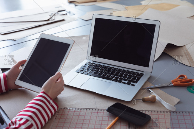 Close up of the hands of a young Caucasian female fashion student using a tablet computer and a laptop while working on a design in a studio at fashion college