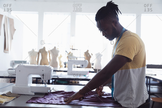 Side view of a young African American male fashion student cutting fabric while working on a design in a studio at fashion college