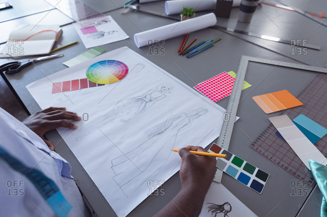 Over shoulder view of a young African American Caucasian mixed race female fashion student working on a design in a studio at fashion college