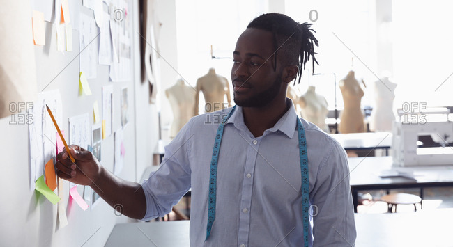 Front view of a young African American male fashion student standing working in a studio at fashion college