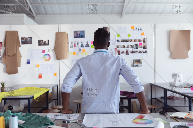 Rear view of a young African American male fashion student looking at drawings on the wall while working on a design looking at designs on a wall in a studio at fashion college