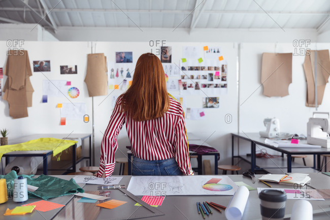 Rear view of a young Caucasian female fashion student looking at drawings on the wall while working on a design looking at designs on a wall in a studio at fashion college