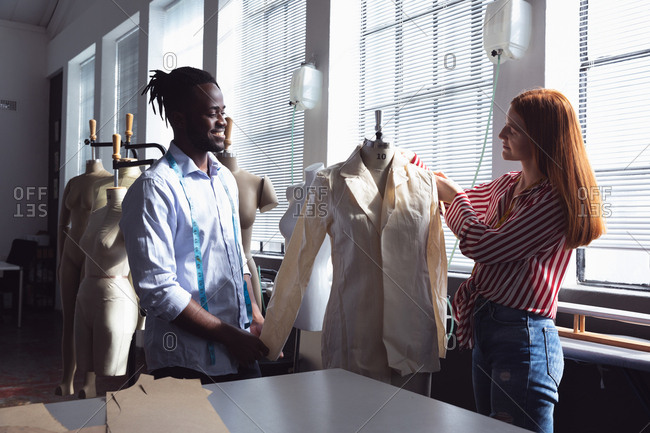 Side view of a young African American male and a young Caucasian female fashion student working together on a design in a studio at fashion college