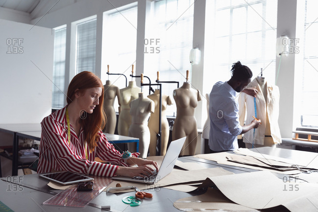 Side view of a young Caucasian female fashion student sitting at a table working on a laptop in a studio at fashion college, with an African American male student working on a jacket design in the background