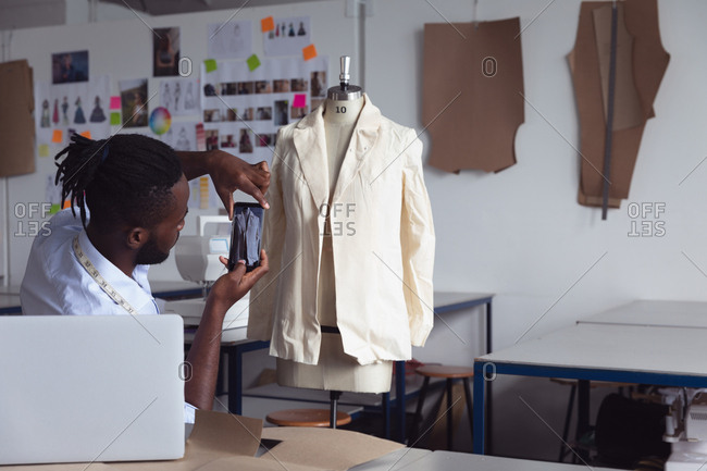 Side view of a young African American male fashion student using a smartphone to take a photo of a jacket design on a mannequin in a studio at fashion college