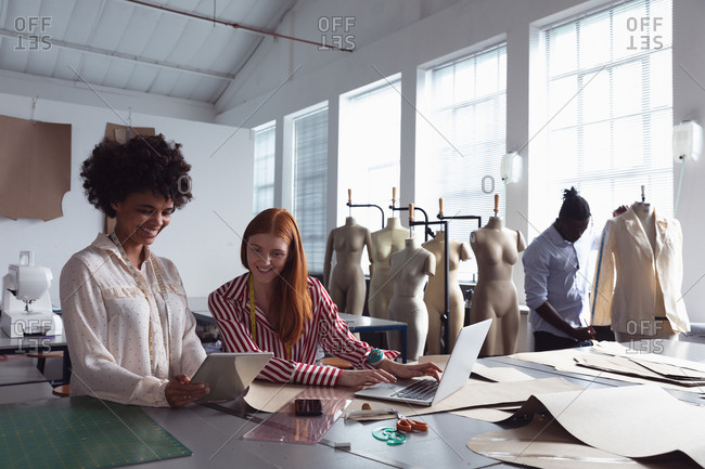 Front view of a young African American female student holding a tablet computer and showing it to a young Caucasian female student using a laptop computer in a studio at fashion college, with a male student working on a jacket in the background