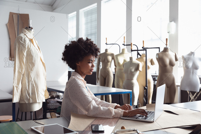 Side view of a young African American female fashion student sitting working on a laptop computer in a studio at fashion college, with mannequins in the background