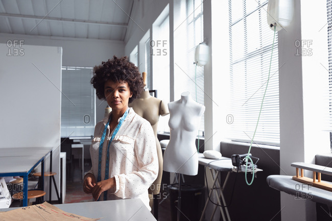 Portrait of a young mixed race female fashion student with a tape measure around her neck smiling to camera standing in a studio at fashion college