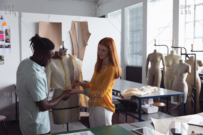 Front view of a young African American male and a young Caucasian mixed race female fashion student working on a design on a mannequin in a studio at fashion college