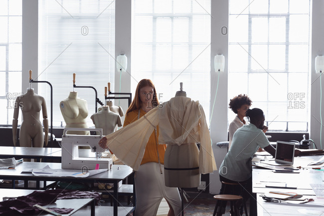 Front view of a young Caucasian female fashion student working on a garment on a mannequin in a studio at fashion college, with opera students working in the background