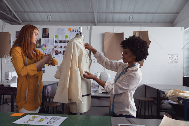 Side view of a young African American and a young Caucasian female fashion student working together on the design of a garment on a mannequin in a studio at fashion college