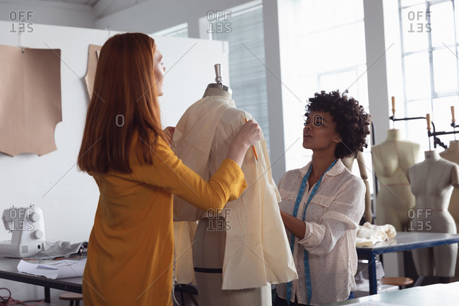 Front view of a young African American Caucasian mixed race female fashion student working on a design in a studio at fashion college